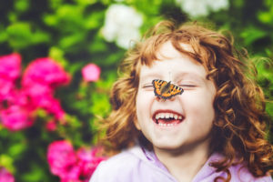 Laughing girl with a butterfly on her nose.
